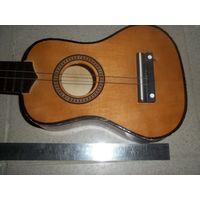 Деревянная маленькая гитара, как настоящая, можно даже сыграть,без трещин, не хватает струн и 2-х барашков